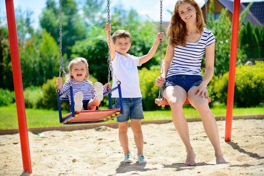 Детские качели, подвешенные к каркасу из металла на цепях