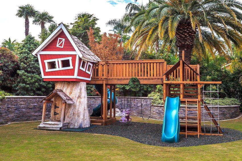 Деревянная горка с двумя спусками, домиком и качелями, построенная во дворе частного дома
