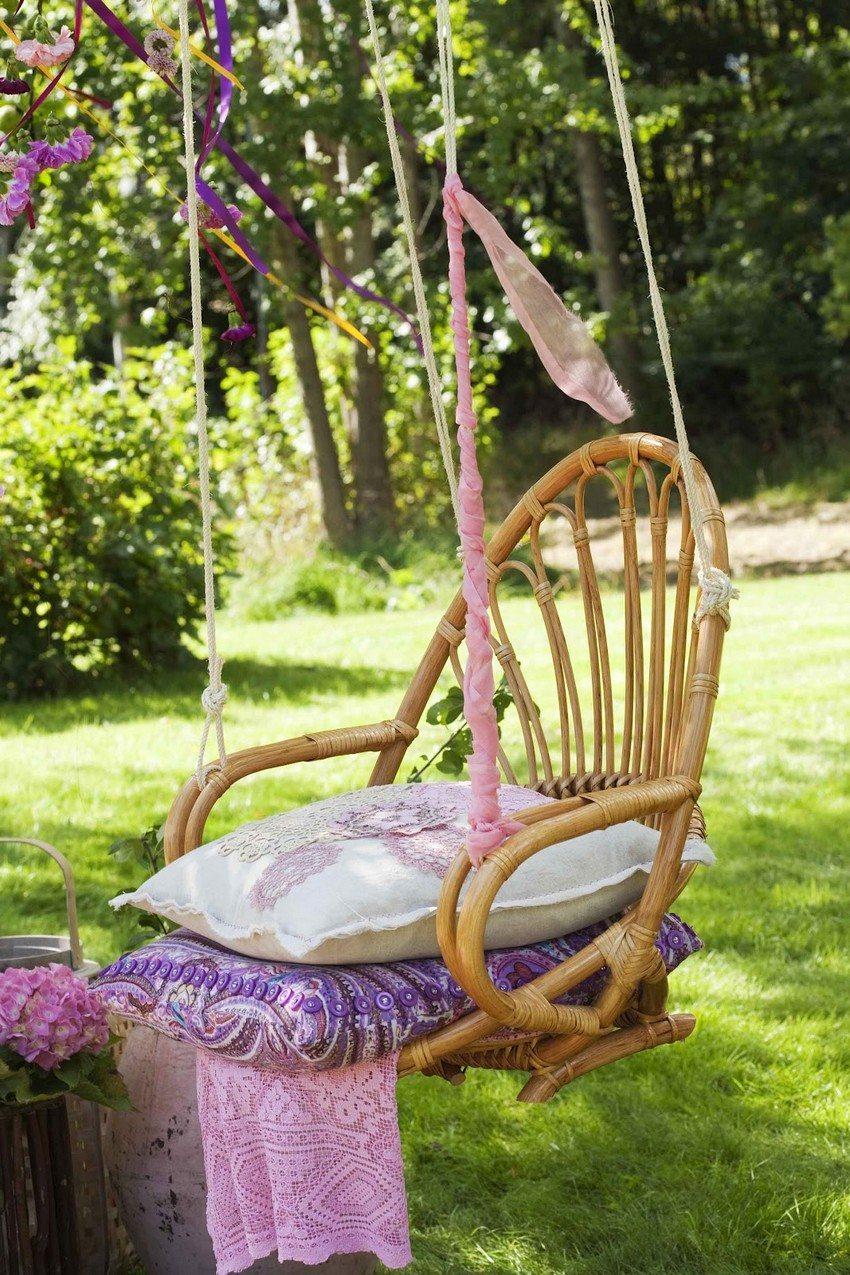 Подвесные качели из плетеного стула, украшенные яркими лентами