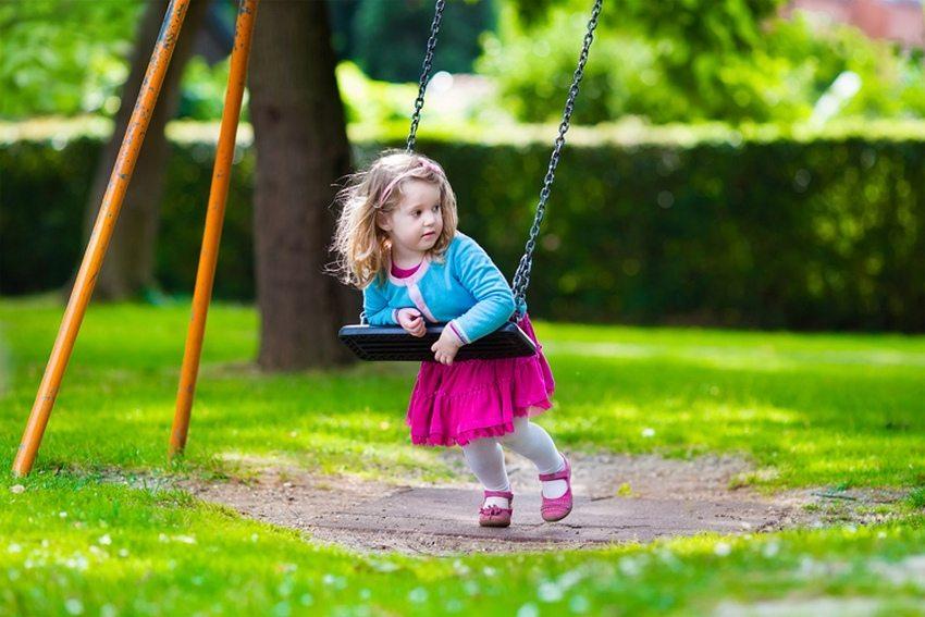 Детские качели, подвешенные к каркасу на цепях