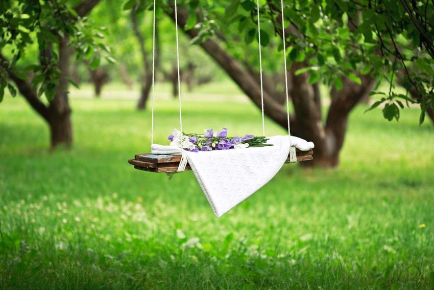 Красивые подвесные качели в саду частного дома