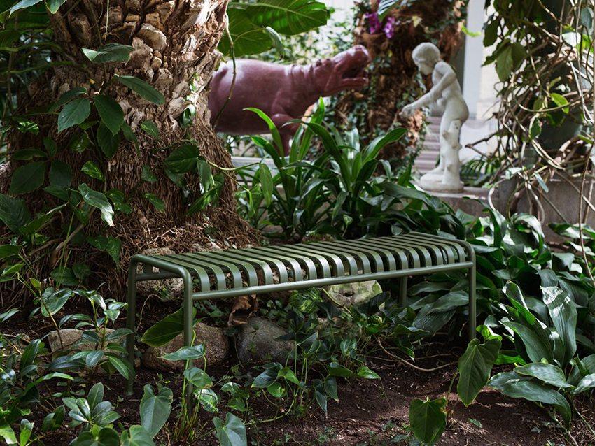 Аккуратная металлическая лавка без спинки в красивом саду