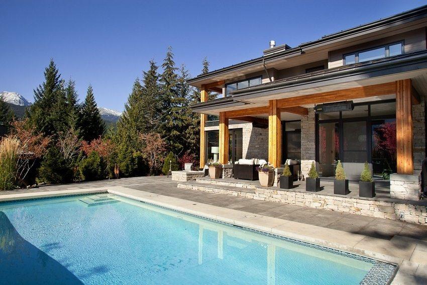 Двухэтажный дом с пристроенным навесом и бассейном на заднем дворе