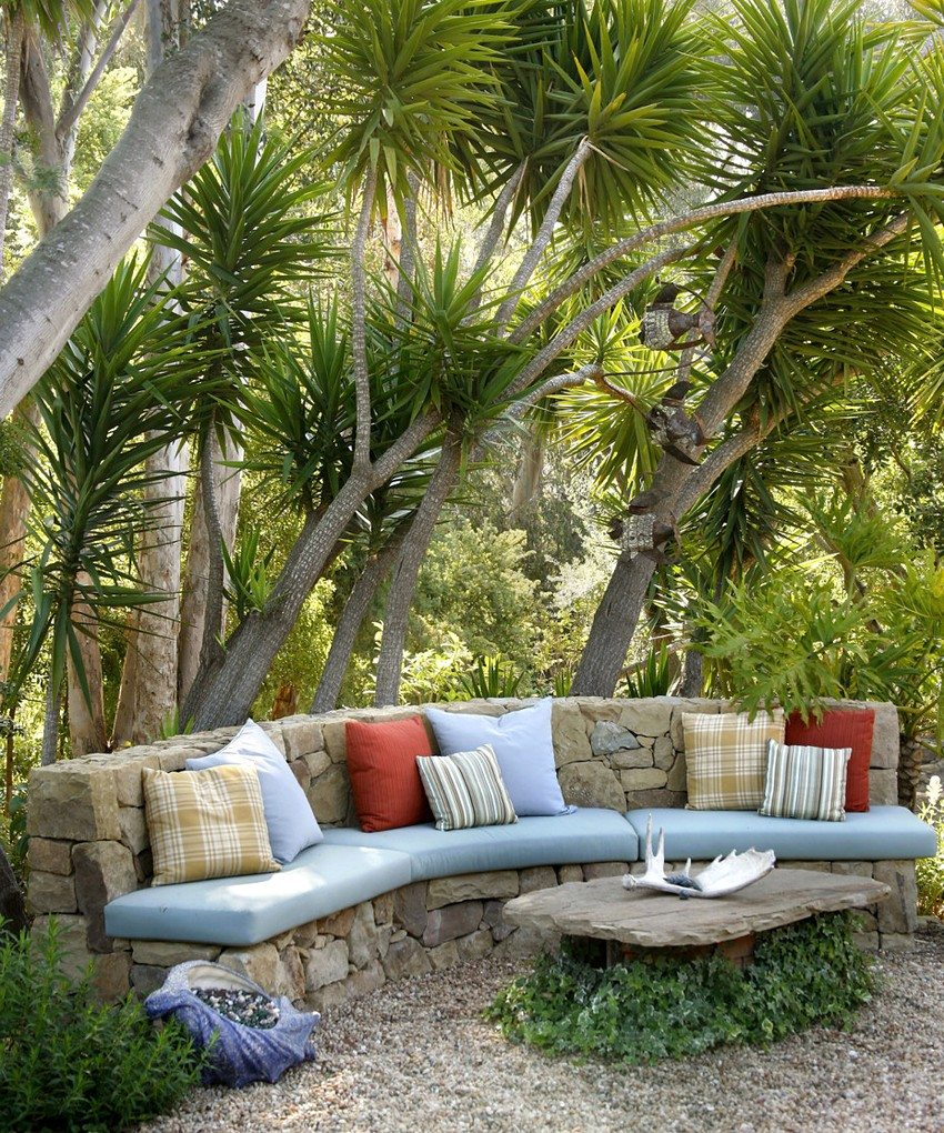 Скамейка, выложенная из натурального камня, с мягкими матрасами и разноцветными подушками