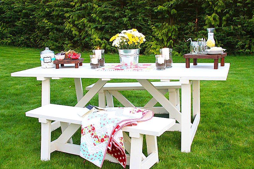 Деревянные стол и лавки, выкрашенные в белый цвет, образуют уютную обеденную зону в саду