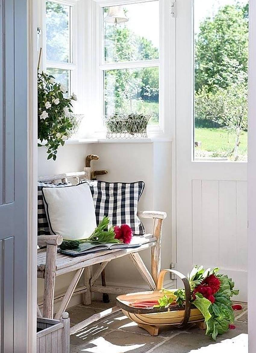 Скамейка из бревнышек установлена на закрытой веранде загородного дома