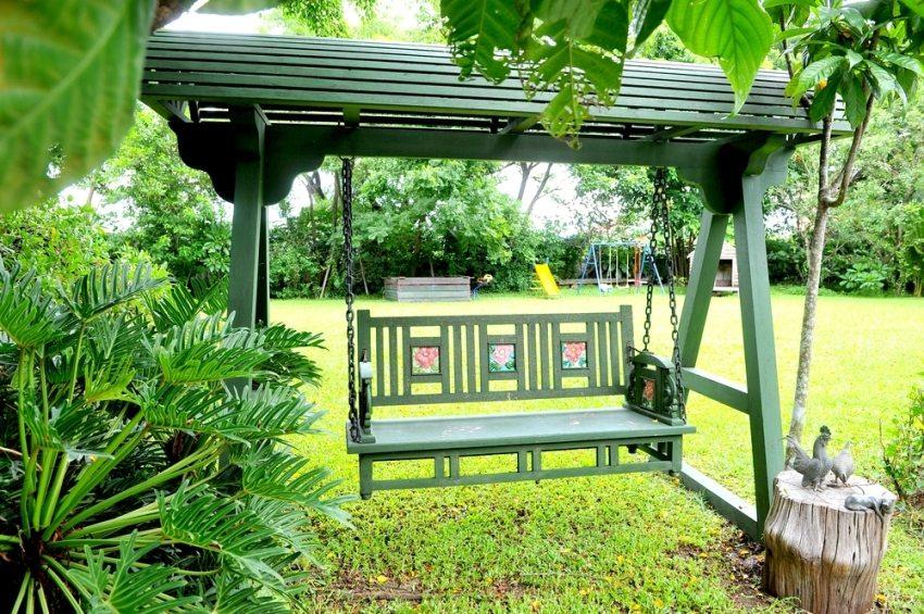 Качели в тихом уголке сада позволят наслаждаться ароматами зелени