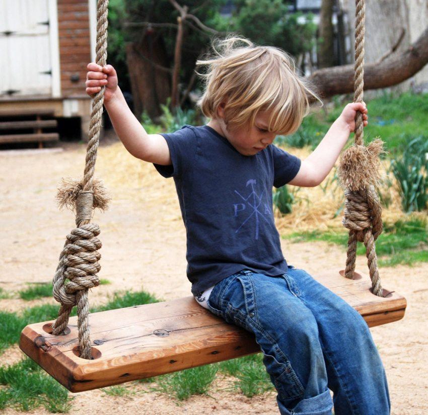 Простые детские качели, изготовленные с использованием деревянной доски и каната