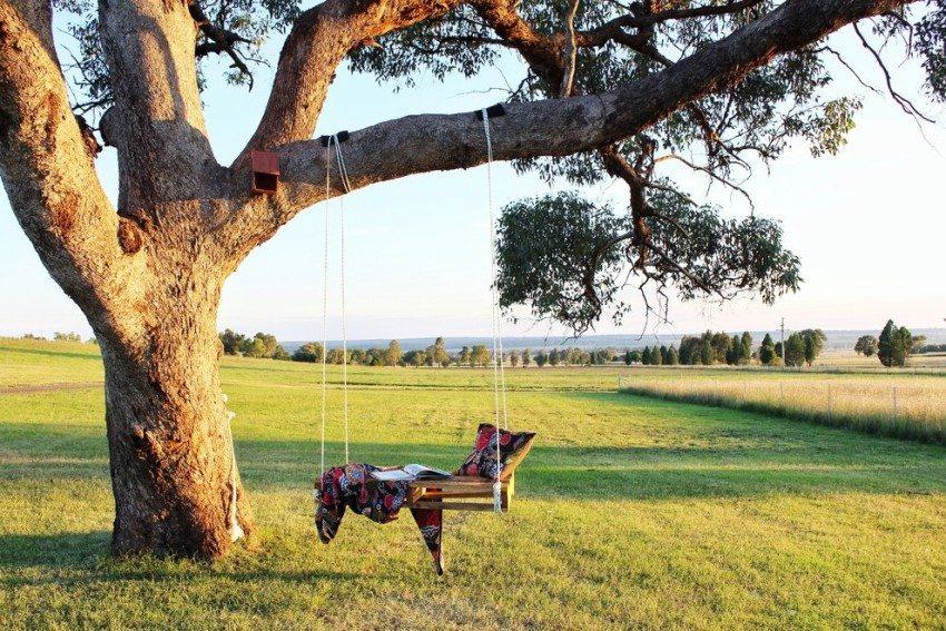 Качели, подвешенные на дерево с помощью веревки