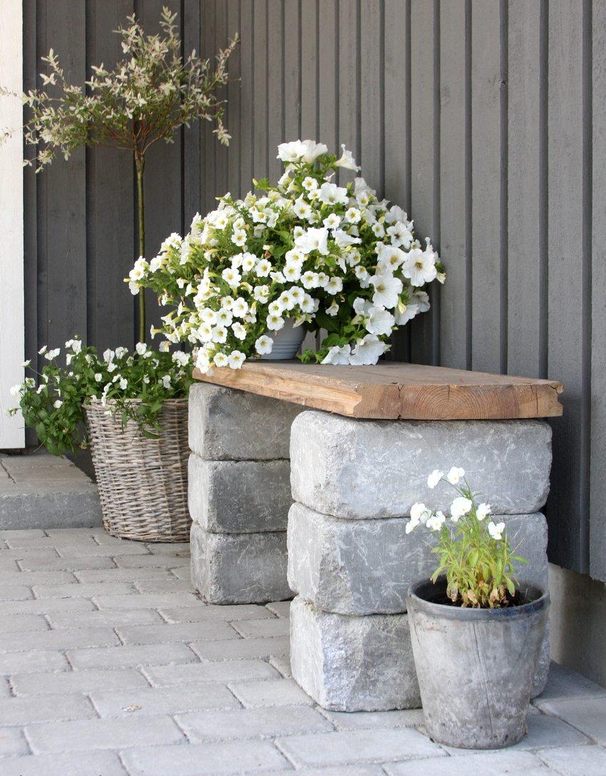 Деревянное сиденье скамейки установлено на бетонные блоки