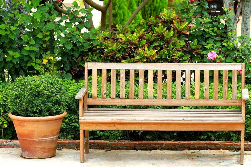 Деревянная скамейка со спинкой и подлокотниками во дворе загородного дома