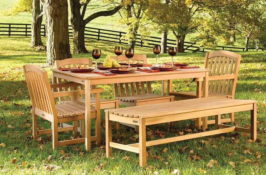 Деревянная скамейка изготовлена в одном стиле с остальной садовой мебелью