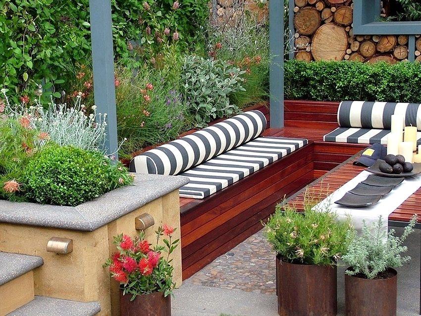 Скамейки из дерева, расположенные под навесом во дворе загородного дома