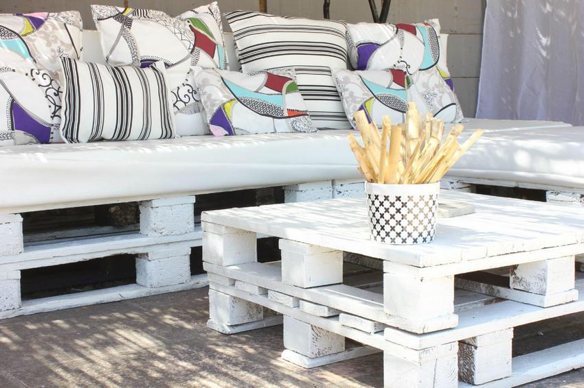 Покрашенная белой краской скамейка из европоддонов с мягким сиденьем и подушками
