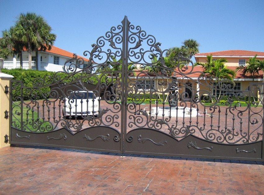 Металлические распашные ворота с обилием ажурных кованых элементов