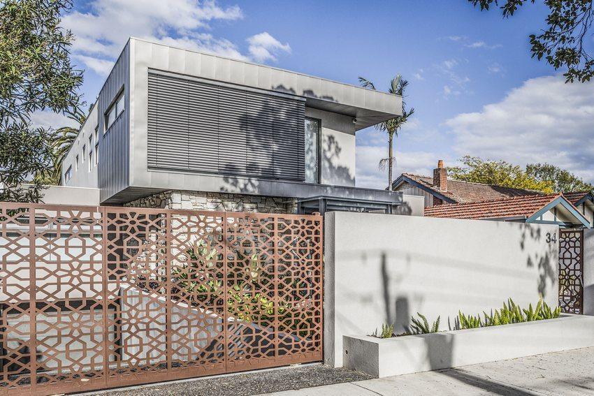 Ажурные ворота и калитка из металла гармонично сочетаются с дизайном здания и придомовой территории