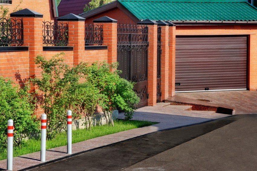 Кирпичный забор с элементами ковки вокруг загородного дома