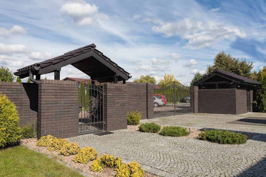 Территория частного дома окружена забором из кирпича
