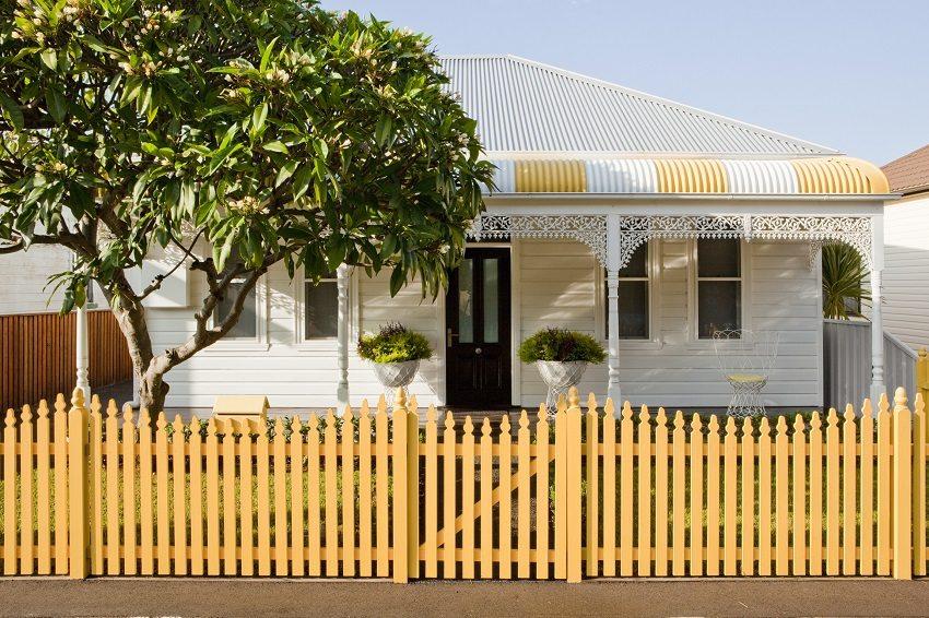Деревянный штакетник, выкрашенный в желтый цвет, служит источником веселого настроения