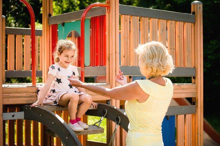 Детский игровой комплекс из древесины с горкой, установленный в саду