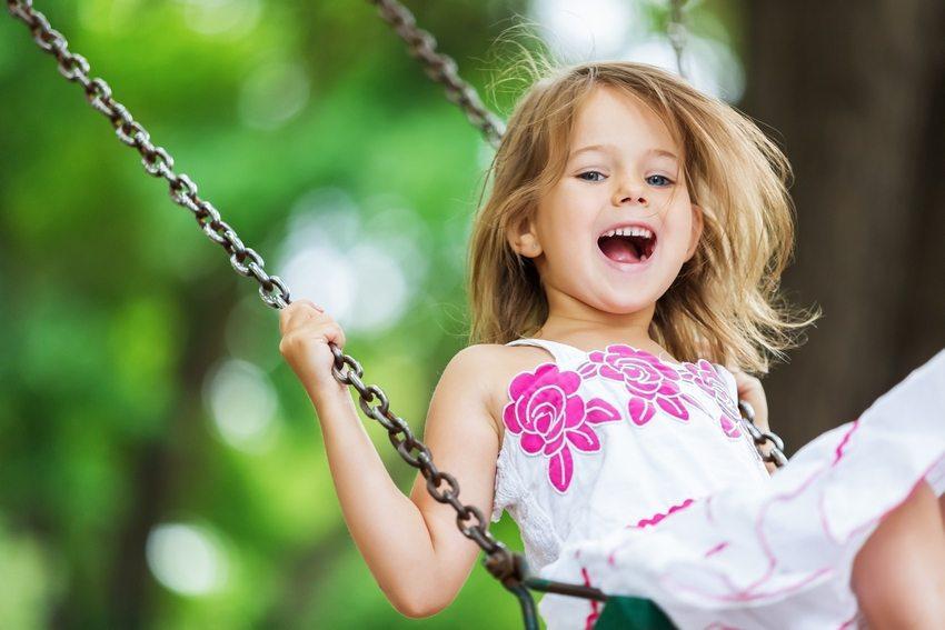 Детские качели, подвешенные к ветке дерева на цепи