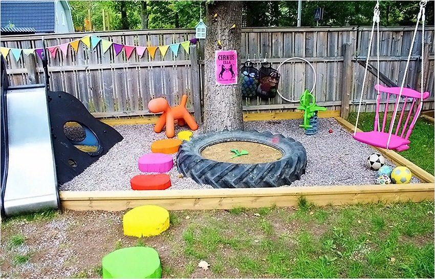 В центре игровой зоны для малышей установлена песочница из старой шины