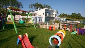 Игровая площадка во дворе частного дома оформлена при помощи использования автомобильных шин, выкрашенных в яркие цвета