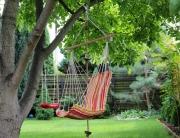 Качели-гамак, подвешенные к дереву, во дворе загородного дома