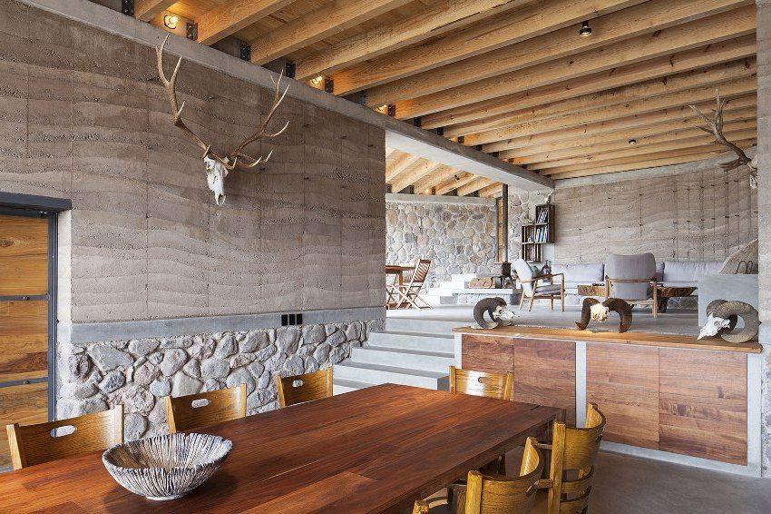 Стильный интерьер из камня, бетона и дерева дополнен скульптурами трофейных животных