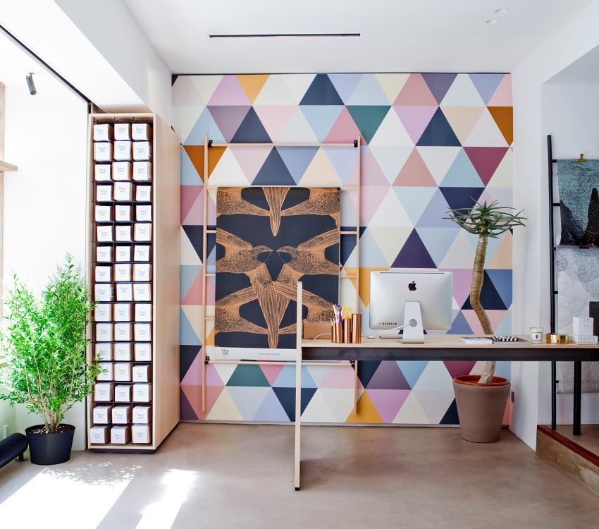 Одна из стен комнаты оформлена обоями с ярким геометрическим принтом