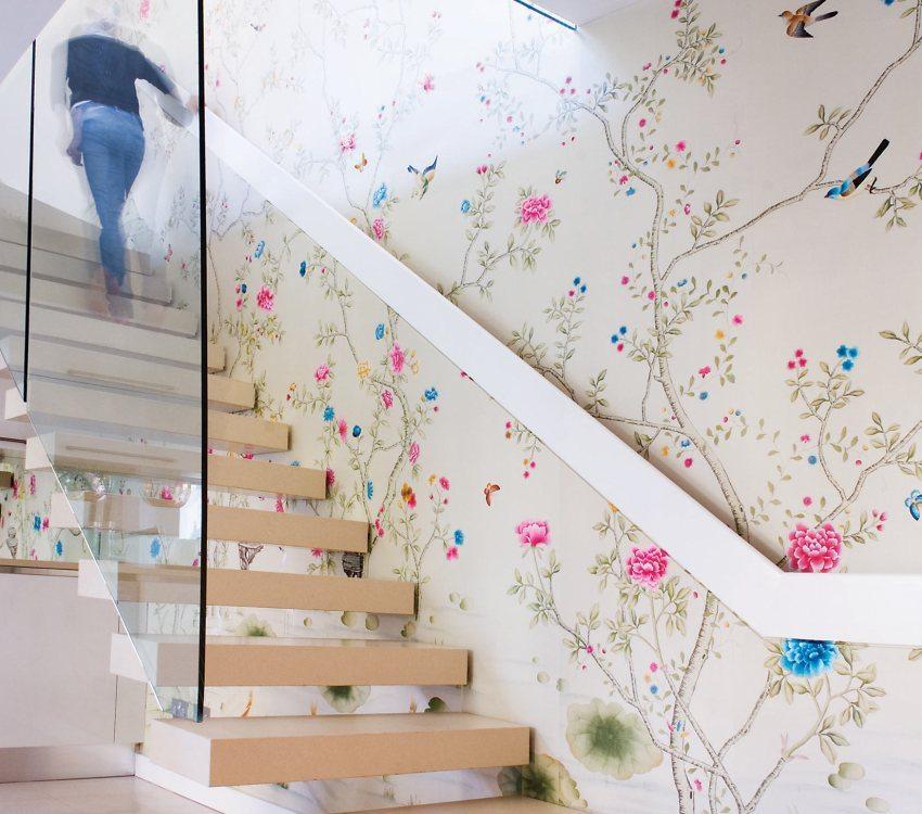 Лестничный холл оформлен светлыми обоями с растительным орнаментом