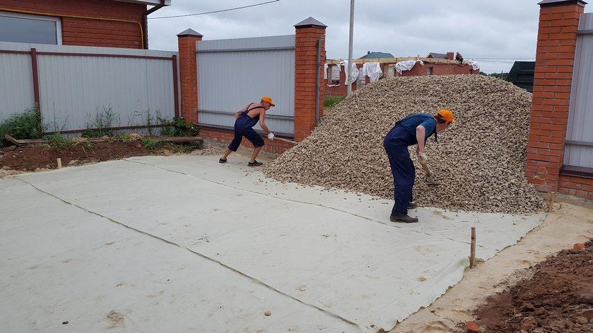 Процесс создания песчано-щебневой подушки. Шаг 2: на уплотненный песок положить геотекстиль, засыпать щебень фракцией 20-40 мм и толщиной слоя 10 см с тромбованием виброплитой
