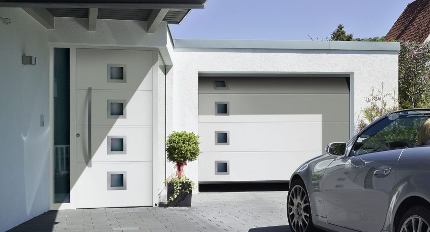 Дверь в дом и ворота выполнены в одинаковом стиле
