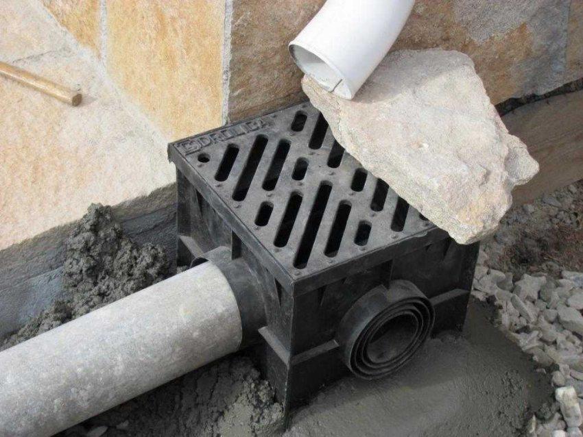 Сохранность и целостность фундамента и отмостки загородного дома обеспечивается установкой пластиковых дождеприемников