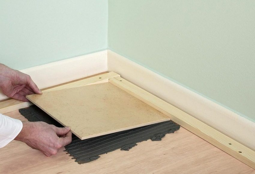 Процесс укладки керамической плитки на деревянный пол