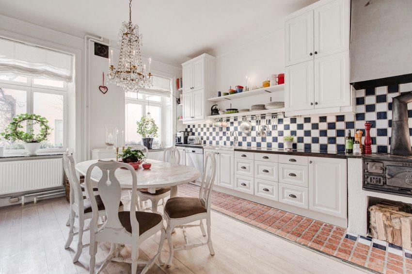 Комбинированный пол на кухне: зона приготовления пищи оформлена плиткой, зона столовой - ламинатом