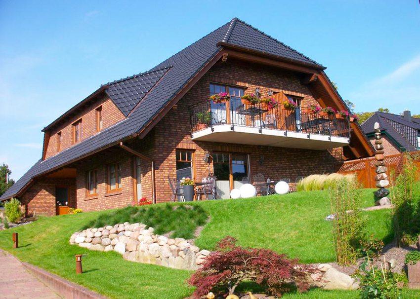 Дом из красного кирпича с полувальмовой крышей