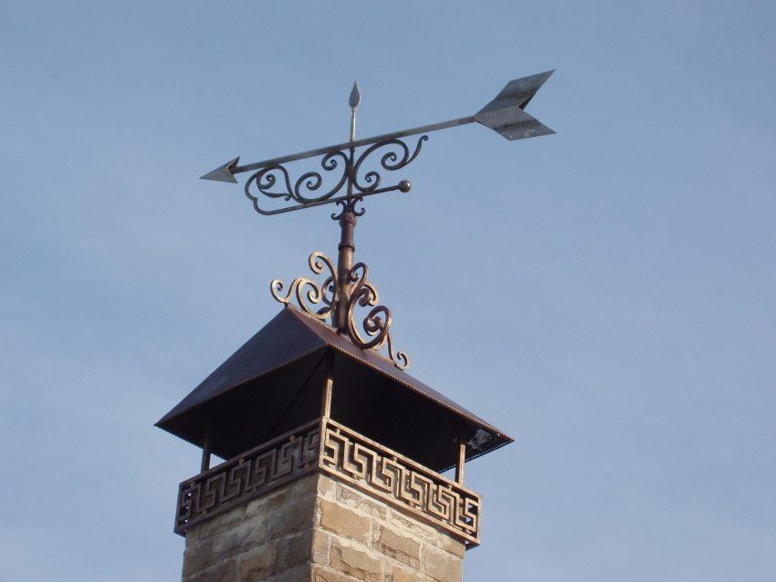 Кованый козырек на дымоход придает эстетичный облик наружной части трубы