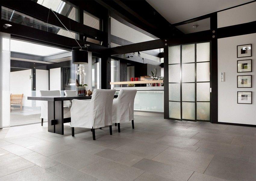 Перегородка раздвижного типа между кухней и гостиной из матового пластика не только функциональна, но и идеально сочетается с общим дизайном помещения