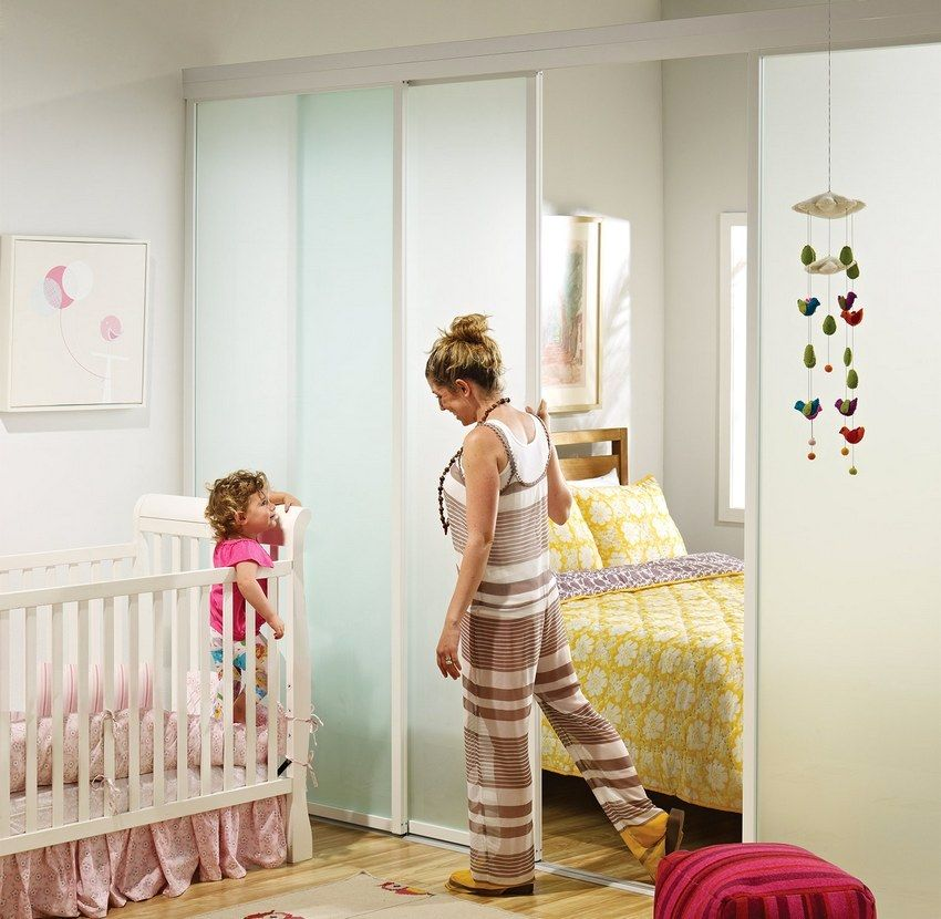 A small living room with a sliding partition is divided into cozy zones - the parents' and children's bedrooms