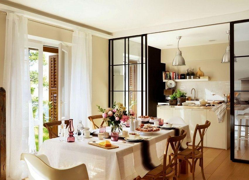 Раздвижная перегородка из стекла и металла установлена между кухней и столовой-гостиной