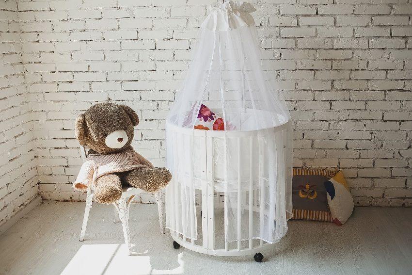 В комнате младенца установлена круглая колыбель с занавесками