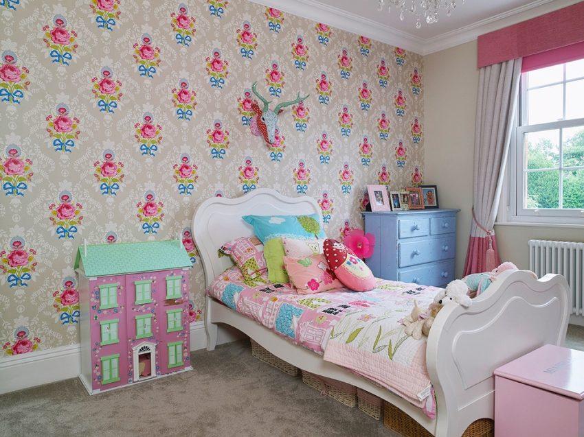 Одна из стен комнаты оклеена бумажными обоями