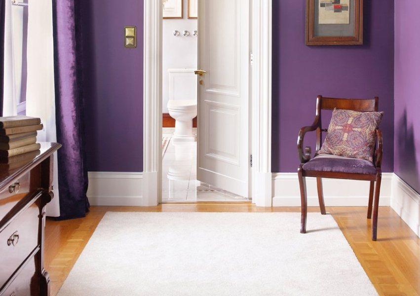 Контрастное сочетание белого плинтуса и яркой фиолетовой стены
