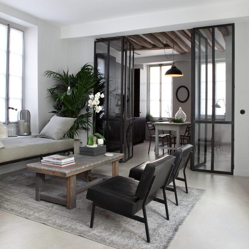 Перегородка с дверцами из стекла и металла отделяет столовую от гостиной