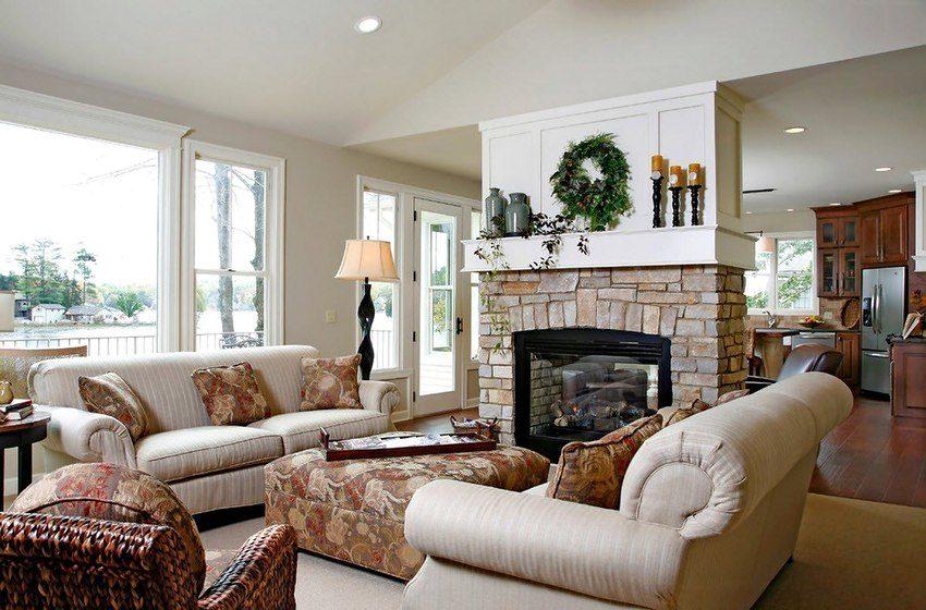 Роль перегородки, разделяющей пространства кухни и гостиной загородного дома, играет камин из гипсокартона