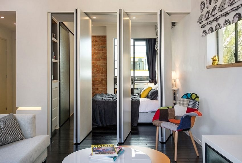 Пластиковая складная перегородка необычной конструкции отделяет спальное место от пространства гостиной