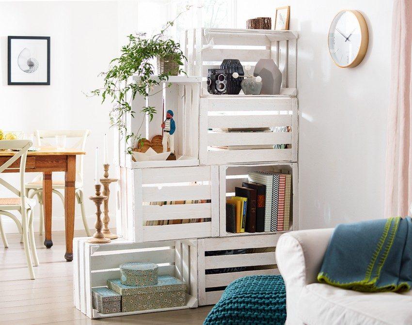 Стеллаж, созданный своими руками из деревянных ящиков, делит пространство небольшой квартиры на зоны и одновременно служит оригинальным украшением интерьера