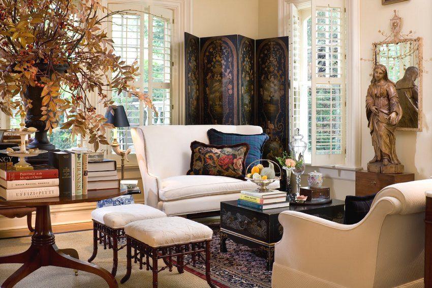 Мобильная перегородка в виде деревянной ширмы с узорами украшает гостиную частного дома