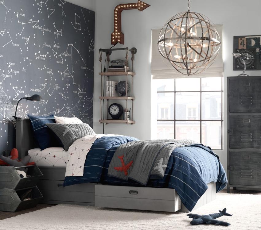 Одна из стен комнаты оклеена обоями с изображением астрологических созвездий